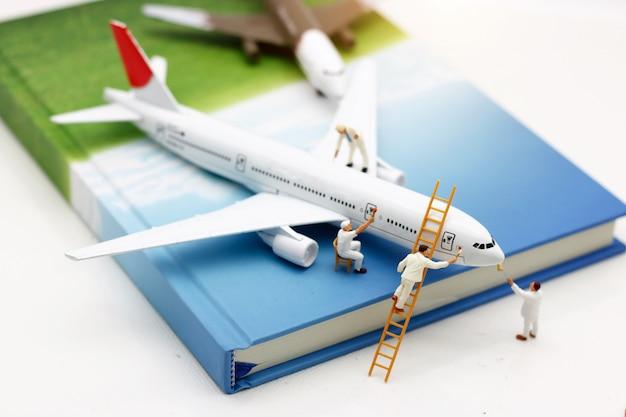 Personnes miniatures: équipe de travailleurs brosse peinture avion. maintenance conceptuelle des avions