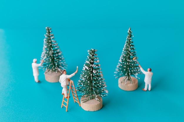Personnes miniatures, équipe de travailleurs peignant sur l'arbre de noël, concept de noël et de bonne année.