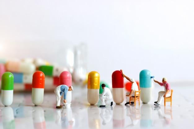 Personnes miniatures: équipe de travailleurs peignant au pinceau des capsules médicinales. concept de soins de santé et médical.
