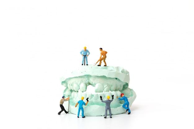 Personnes miniatures: équipe de travailleurs réparant une dent