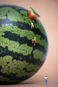 Personnes miniatures escalade pastèque