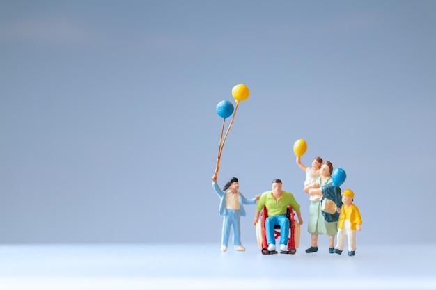 Personnes miniatures famille positive prenant soin de leur père handicapé