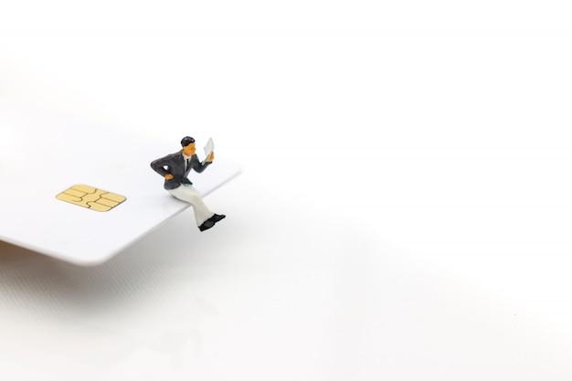 Personnes miniatures: homme d'affaires, lecture de livre sur carte de crédit.