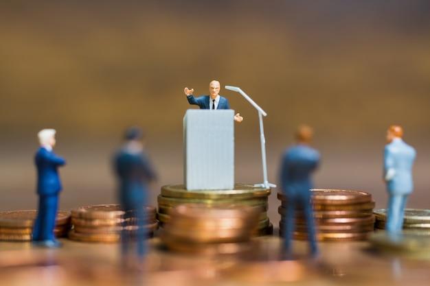 Personnes miniatures: homme d'affaires parlant sur le podium