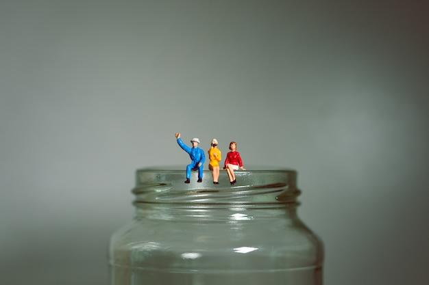Personnes miniatures, homme et femme assis sur une bouteille de verre