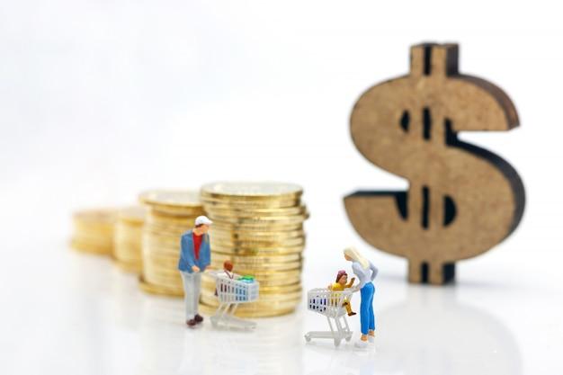 Personnes miniatures: parents et enfants avec carte d'achat debout devant la pile de pièces et le signe dollar.
