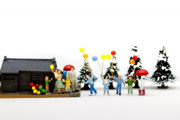 Personnes miniatures, parents et enfants tenant un ballon avec la maison.