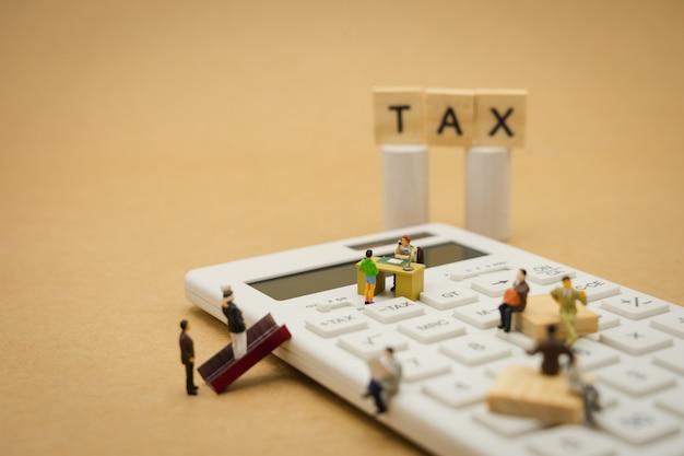 Personnes miniatures payer le revenu annuel (tax) de la file d'année sur la calculatrice.