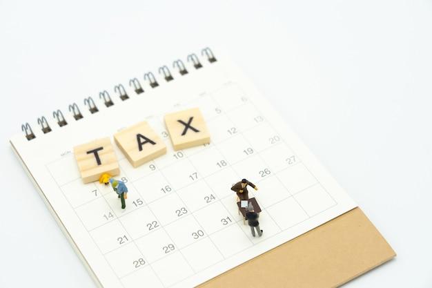 Personnes miniatures payer le revenu annuel (tax) de la file d'attente pour l'année sur le calendrier.