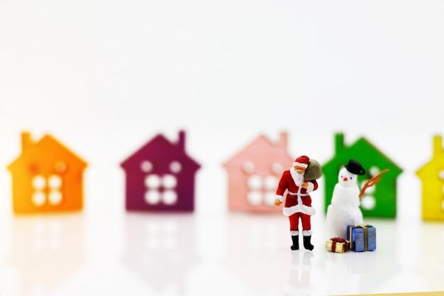 Personnes miniatures: père noël et bonhomme de neige avec cadeau debout devant le modèle de maison en bois.