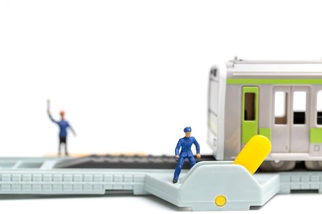Personnes miniatures: le personnel des chemins de fer travaille au chemin de fer sur fond blanc