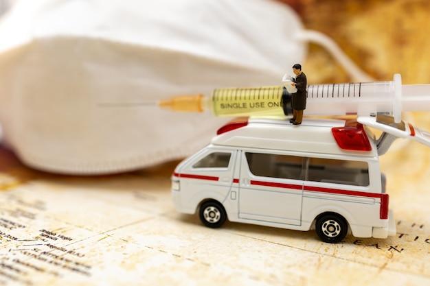 Des personnes miniatures se tiennent sur une ambulance avec un masque médical et une seringue de vaccin covid-19. vaccin et santé concept médical.