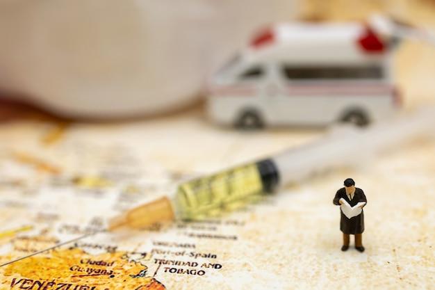 Des personnes miniatures se tiennent sur la carte du monde avec une ambulance, un masque médical et une seringue de vaccin covid-19. vaccin et santé concept médical.