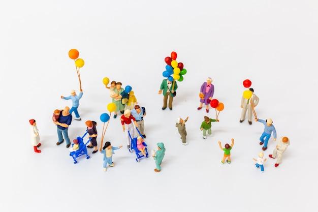 Personnes miniatures tenant ballon isolé sur blanc