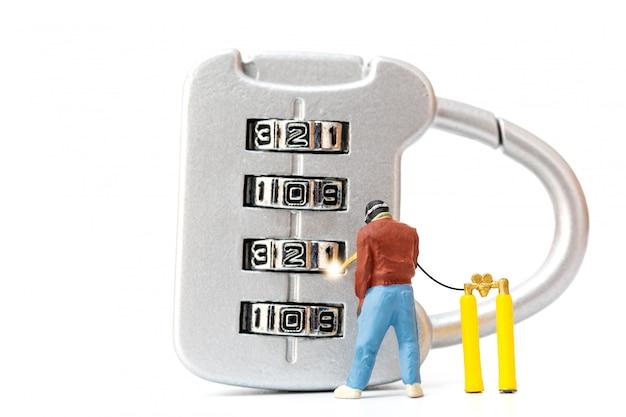 Personnes miniatures travaillant sur le cadenas à combinaison numéro 2020