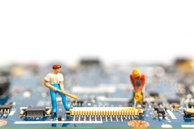 Personnes miniatures travaillant sur carte cpu
