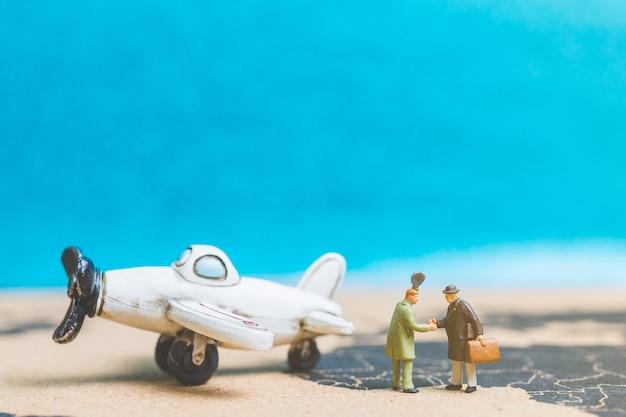 Personnes miniatures: voyageurs avec avion sur la carte du monde