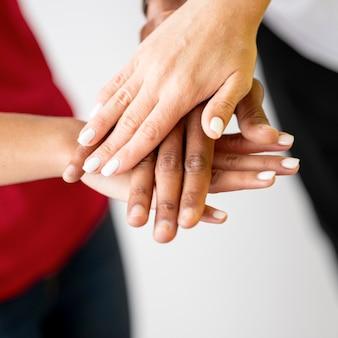 Personnes multiraciales mettant leurs mains ensemble