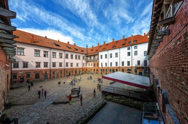 Des personnes non identifiées marchent près du château de mir dans la région de grodno, en biélorussie. le château est une fortification défensive xvi-xvii siècle