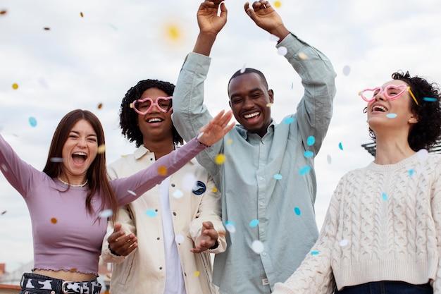 Personnes à plan moyen faisant la fête avec des confettis