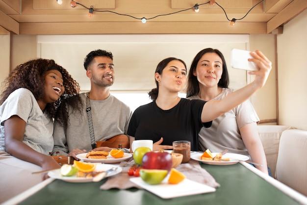 Personnes à plan moyen prenant un selfie avec un téléphone