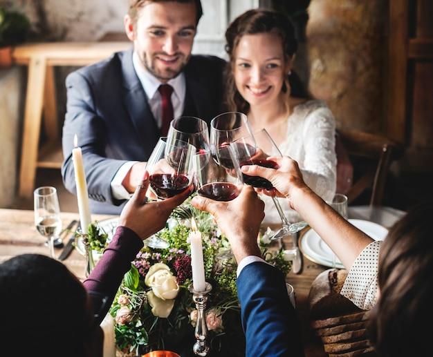 Personnes portant des verres à vin lors d'une réception de mariage avec les jeunes mariés