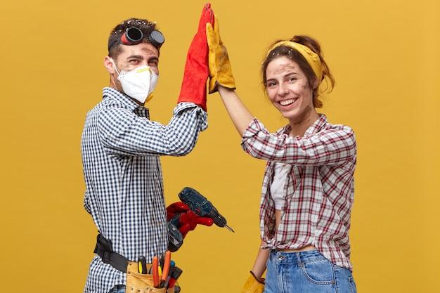 Personnes, profession, travail d'équipe, concept de coopération. caucasian couple debout sur le côté faisant des travaux de construction à la maison en touchant leurs mains ensemble se réjouissant de leur succès et d'excellents résultats