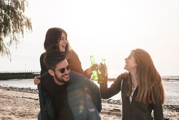 Personnes qui sonnent des bouteilles de bière près de la mer