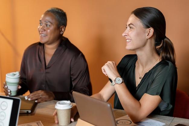 Personnes souriantes à plan moyen au bureau
