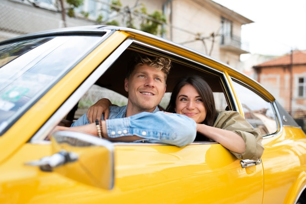 Personnes souriantes à plan moyen en voiture