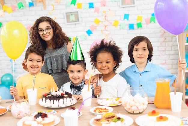 Personnes et table de fête enfants célébrant une fête d'anniversaire