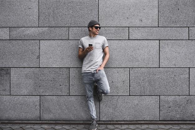 Personnes, technologie, voyages et tourisme - homme avec écouteurs, smartphone dans la rue de la ville et écoutant de la musique sur fond de mur gris