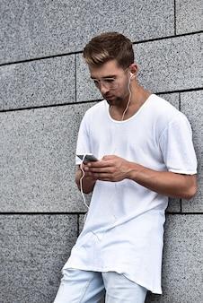 Personnes, technologie, voyages et tourisme - homme avec écouteurs, smartphone dans la rue de la ville et écouter de la musique sur fond de mur gris. notion d'écouteurs.