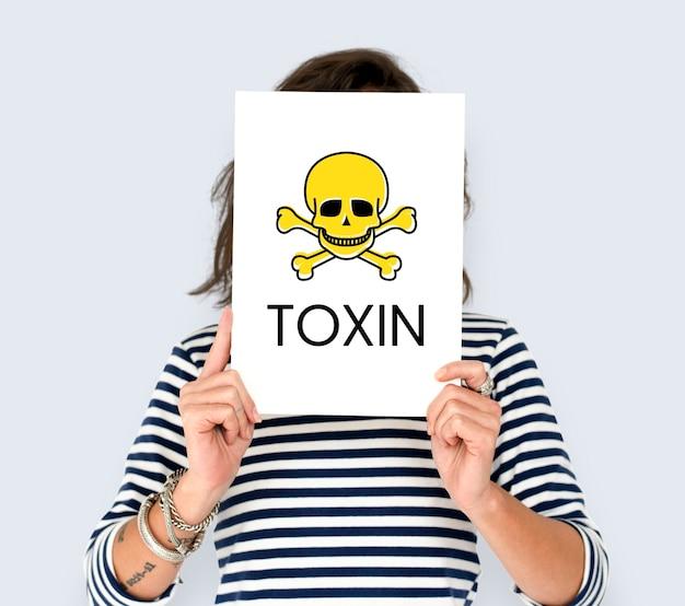 Personnes tenant une pancarte avec une icône de crâne et des produits chimiques dangereux