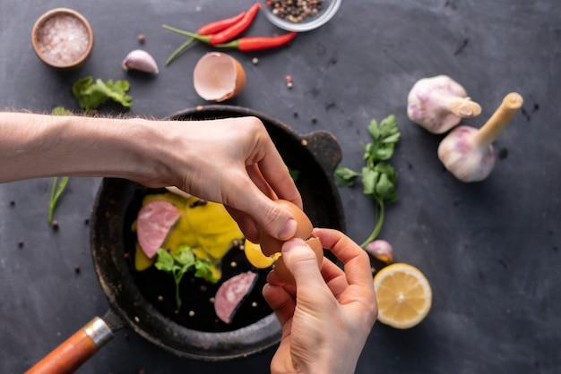 Des personnes tiennent un œuf fêlé à la main et versent un jaune et des protéines dans une poêle pour le faire cuire, à la mode rustique