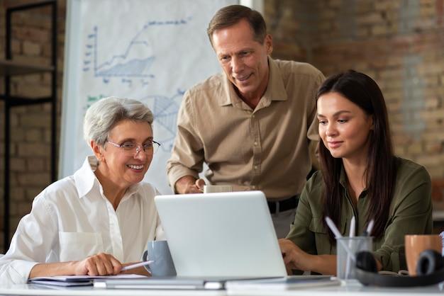 Personnes utilisant un appareil numérique lors d'une réunion