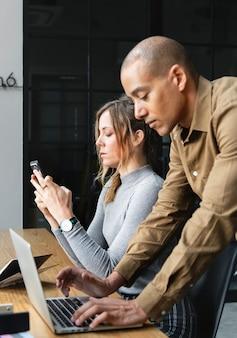 Personnes utilisant des appareils numériques pendant une pause