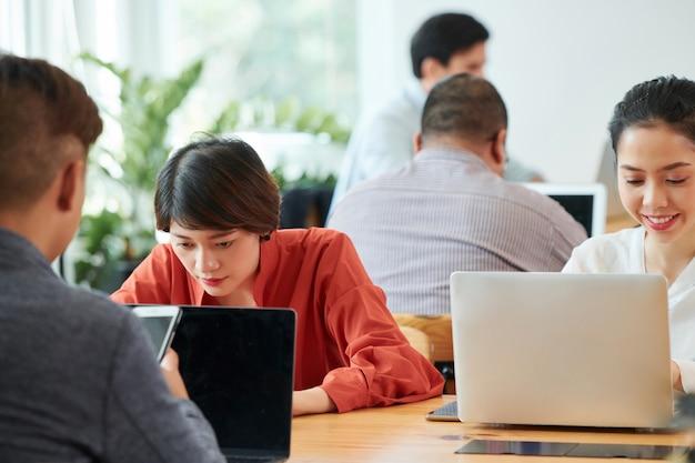 Personnes utilisant des ordinateurs portables au bureau
