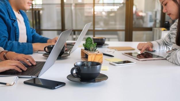 Personnes utilisant et travaillant sur un ordinateur portable et une tablette sur la table au bureau