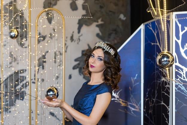 Personnes, vacances et concept de mode. heureuse jeune femme en robe bleue et couronne de princesse sur fond brillant festif. portrait de la belle jeune fille avec une couronne sur la tête. peau fraîche et propre