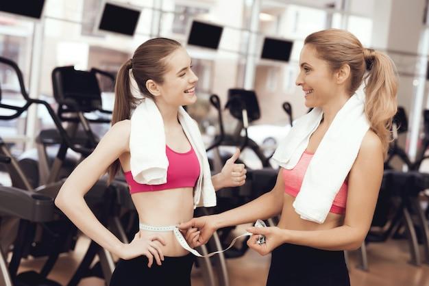 Personnes en vêtements de sport mesurant la taille de la fille à la salle de gym.