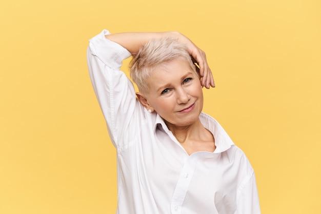 Personnes, vieillissement, maturité, beauté, soins de la peau et concept de santé. belle femme mature élégante avec coupe de cheveux teinte lutin pliant la tête et tenant la main sur la joue à faire des exercices, souriant