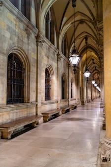 Perspective arquée avec des colonnes anciennes, plafond voûté suspendu à de vieilles lampes et bancs en pierre le long du mur du temple de vienne, en autriche.