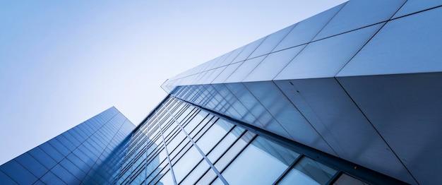 Perspective, le gratte-ciel est dirigé vers le ciel. dégradé bleu, réflexion de la lumière dans le verre, conception de bâtiments urbains