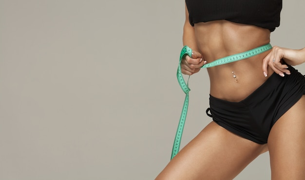 Perte de poids, corps mince, concept de mode de vie sain. fit fitness girl mesurant son tour de taille avec du ruban de mesure sur gris