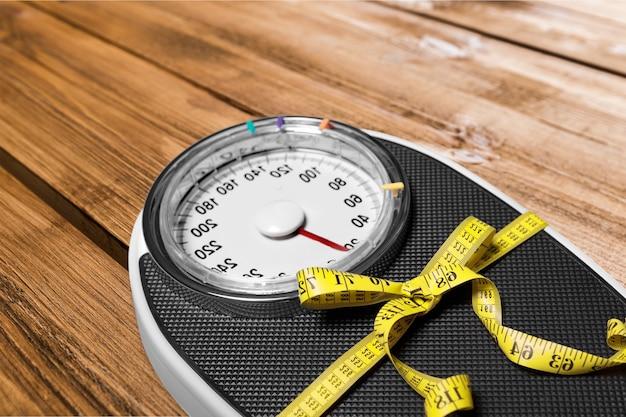 Pèse-personne avec un ruban à mesurer sur fond