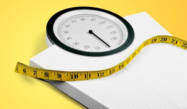 Pèse-personne avec un ruban à mesurer isolé sur fond
