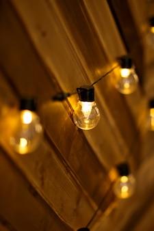 Pesez les ampoules sur un mur en bois. brûler des guirlandes de guirlande sur un fond en bois. ampoules sur un fond en bois.