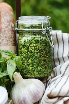 Pesto en pot de verre avec des ingrédients basilic, pignons de pin et pain à l'extérieur