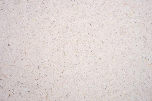 Pétale de fleur de mûrier de riz brun clair et graine fabriqués à la main fond de papier rugueux texturé.